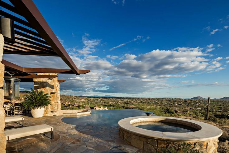 Situated along the Arizona hillside, this Southwestern home features a spacious flagstone patio with a magnificent view of the valley. Multiple seating areas, a two-sided fireplace, negative edge pool and an outdoor kitchen make this a luxury outdoor space to enjoy company.