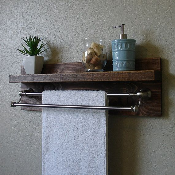 Handmade bathroom shelf with a brushed nickel double towel bar. A perfect addition to any home bathroom or apartment.  Made from solid wood. It has been lightly sanded down, then stained and sealed with a beautiful dark walnut finish.  This piece does not include the accessory items as shown in the pictures.  The color of the stained wood captured in the photos might vary slightly.  Dimensions: 29 in wide x 9.25 in tall x 4/6 in deep (shelf 3.5/5.5 in deep)  Keyhole hangers are installed on…