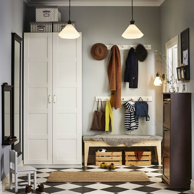 A hallway with a white wardrobe and a brown shoe cabinet that holds at least 12 pairs of shoes. Shown together with a bench in solid pine and two white knob racks.