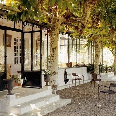 Domaine de Larbeou in Bayonne, France. front porch with glazed metal windows shaded by plane trees.