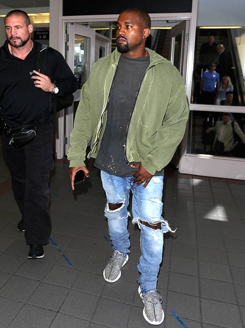 Kanye West sports Haider Ackermann Hoodie, Fear of God LA Jeans and Yeezy 350 Boost Sneakers at LAX #kanyewest #haiderackermann #hoodie #fearofgod #fearofgodla #jeans #yeezy #yeezy350boost