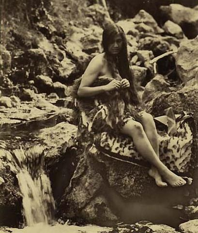 Woman posed in korowai next to stream.