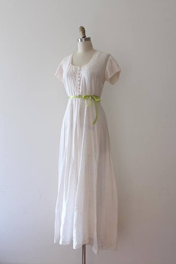 Gorgeous sheer lightweight maxi dress from the 1940s. This gown features a great textured fabric with dots in yellow over the sheer white, a fitted waistline (waistline is a little high), and early plastic buttons.
