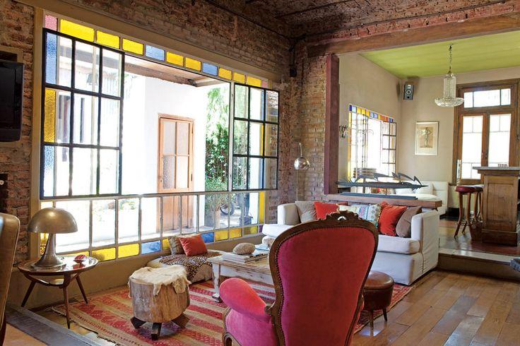 Living con gran ventanal de vidrio repartido en una casa reciclada del Bajo San Isidro.