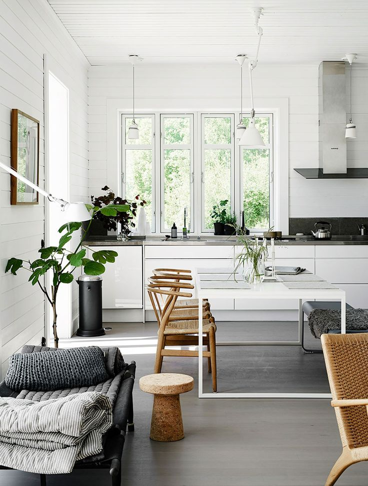 Beautiful dining room that has natural materials, textures and colors - grey floor, wishbone chairs and bare windows