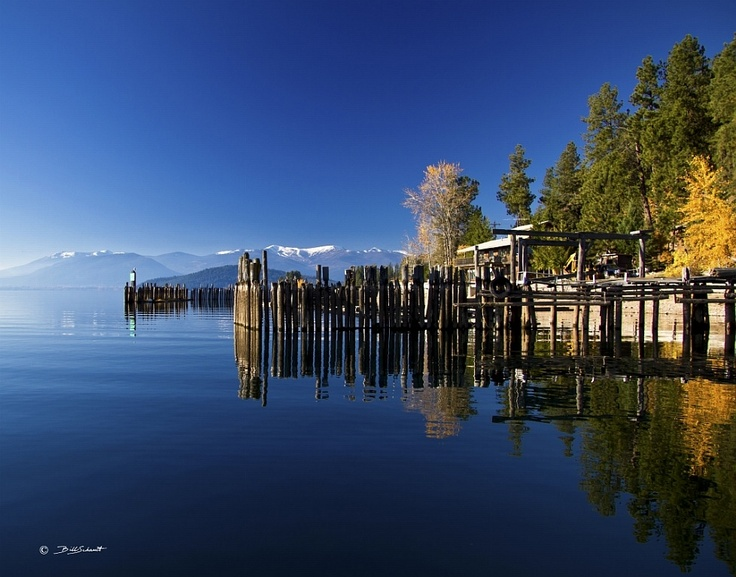 Schweitzer Ski Resort from the Boatworks Marina at Sunnyside Point on Lake Pend Oreille. This shows a dusting of snow on the runs in early November of 2010. Also Fall colors and pilings reflected. Located near Sandpoint, Idaho. Photo 4 in a series of both color and black and white.