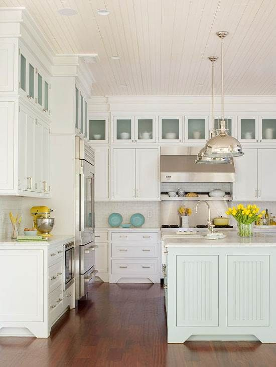 A sea-inspired color scheme of robin's egg blue, warm white, and splashes of contemporary sheen update the look of this classic coastal kitchen design and remodel. Shaker-style cabinetry and beaded-board panels on the kitchen island. By OTM Designs & Remodeling Inc.
