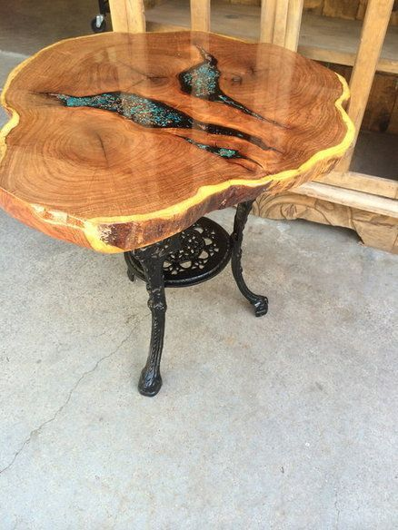 Mesquite slab with a cast iron base. Chrysocolla and copper with black sand were used for filler and an clear epoxy flood coat finish. A beautiful table: