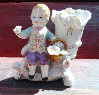 Available now from Orphaned Treasures ~ 1950s Vintage China Porcelain Boy and Flower Basket Vase Delicate and Detailed. $15.35, via Etsy.