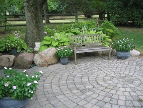 Radial balance is seen here in a perfectly round cobblestone patio in a quiet shade garden. Think about how ordinary this space would appear with a traditional flagstone patio or a concrete slab. Using the radial design both energizes and enlivens the garden.