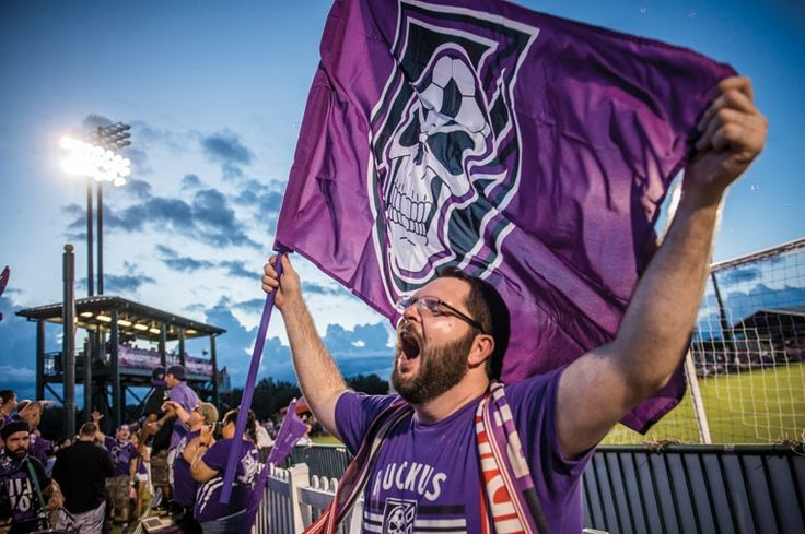 A Ruckus fan waves the group's flag during an Orlando City playoff game last year.  From cheering and singing to pyrotechnics, Orlando City's raucous supporters are a special breed.