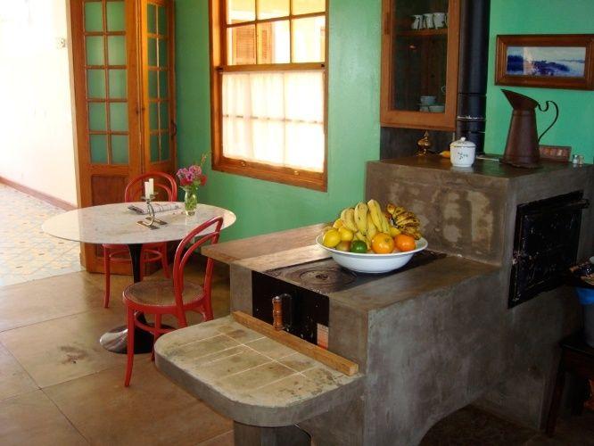 O fogão à lenha, em cimento queimado, ladeia o canto de almoço formado pela mesinha e as duas cadeiras Thonet e serve como aparador, quando não está sendo usado para a cocção. A cozinha de fazenda foi projetada pelo arquiteto René Fernandes.  Fotografia:  Divulgação.