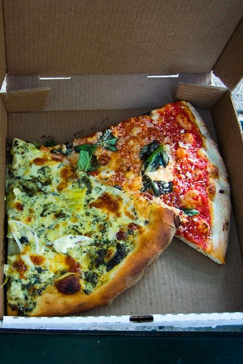 A hot slice from Artichoke Basille's. | 21 Delicious NYC Foods That Won't Break The Bank