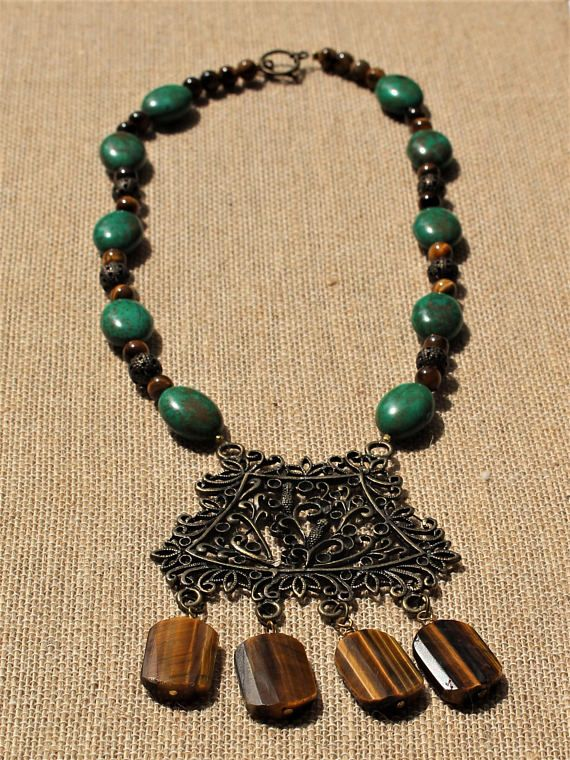 The Wood Nymph-Genuine Tigers Eye Gemstone and Deep Forest Green Magnesite Stone Necklace  The deep green pine trees sway atop the large brown trunks. Deep in the forest there is a sprite-ly stirring, the stirring is the movement of the wood nymphs. This necklace is made using shimmering brown tigers eye stone beads and deep, forest green magnesite beads. The bronze pendant is large and immensely detailed with ivy and leaves.