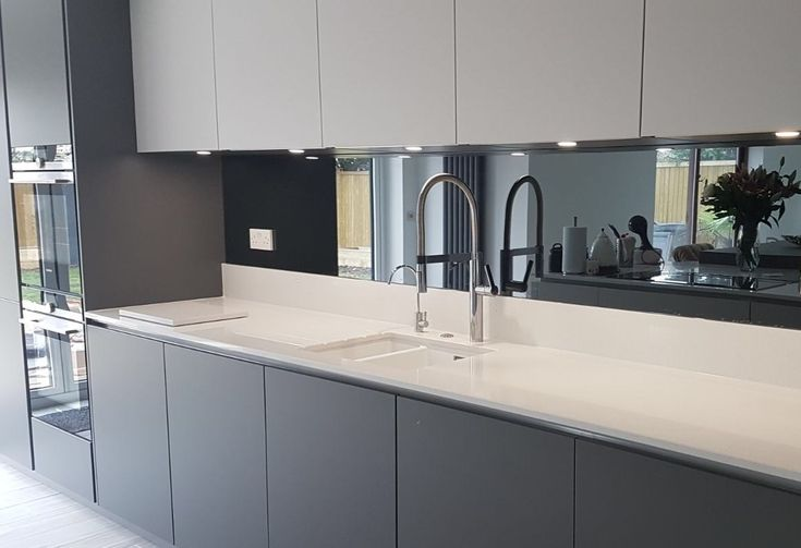 Grey mirrored glass kitchen splashback complementing this kitchen.