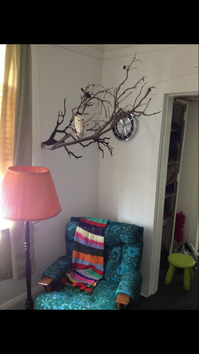 DIY bring a 2D branch wall decal to life by suspending a branch from the ceiling and placing it as if it's coming out of the decal
