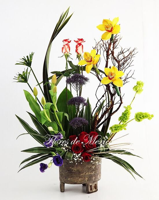 Precioso diseño de exóticas orquídeas, tulipanes, rosas y follajes selectos en fina maceta con grabados prehispánicos de gran valor artesanal.