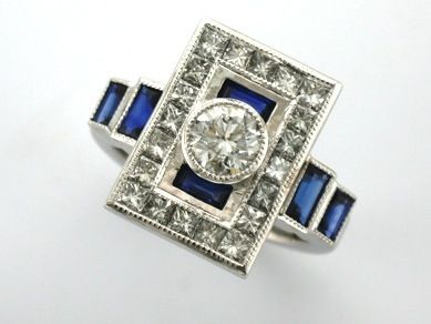 'JANINE' --  Stunning Art Deco Style Ring Custom made with Client's Brilliant Cut  & Princess Cut Diamonds in 18ct White Gold.  Baguette Cut Sapphires were added for Colour and to complete this Fabulous Design.'