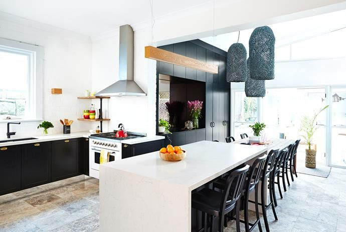Serial renovator and The Block co-creator David Barbour takes on the challenge of redesigning his own kitchen. A combination of black and natural timber is subtly repeated throughout the kitchen and dining area. Timber pendant light from Beacon Lighting. Benchtops in London Grey from Caesarstone.