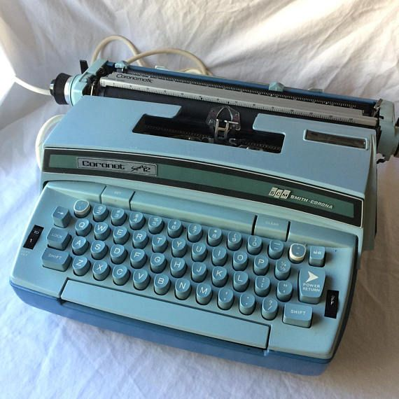 This is a vintage blue Smith Corona Coronet Super 12 Coronamatic Electric Typewriter. The machine is working and is in generally clean condition. Note that this machine takes a special ribbon cartridge not a spooled system. These special ribbons are still available from office supply