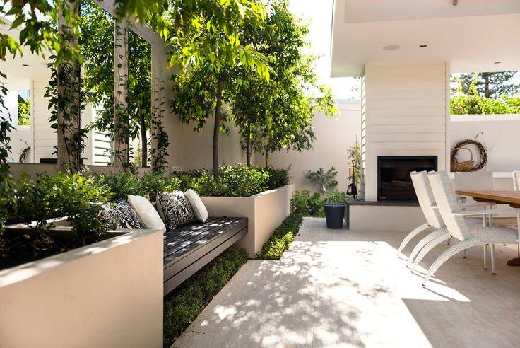 Planteringen som ramar in terrassen rymmer också extra sittplats.