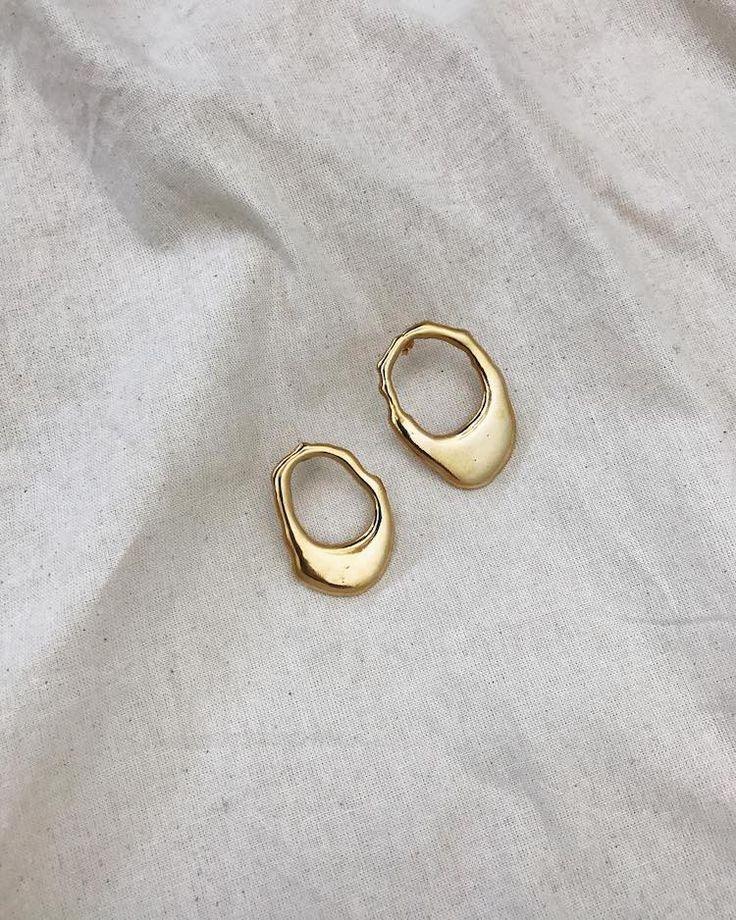 Minimalist style jewellry gold earrings on white linen.