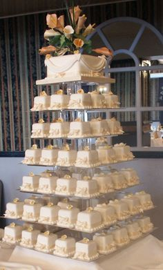 100 square Mini Wedding Cakes with top cake for cutting, cream and gold Calla Lilly display to the top cake.  http://www.annescakecreations.co.uk/mini_cakes.html
