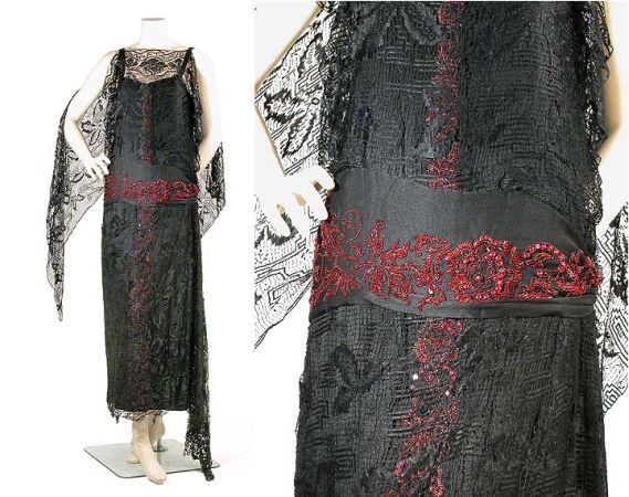 Black Silk Lace and Faux Garnet Evening Dress   Attributed to Poiret, mid 1920s   A full length chemise of black crepe backed satin marked by a radiating center panel embroidered with faux garnet beads in a floral motif, the slip bodice overlaid with geometric blonde style black lace with floating rectangular panel of same at either side of back, lace overlaying skirt concluding in deep narrow points, hip band of satin with faux garnet embroidery, size 6