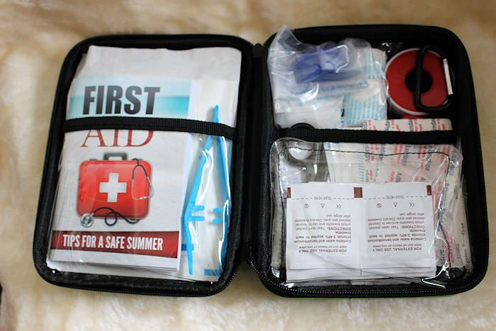 There is a first aid guide book in it as well as CPR face mask and valve, sterile eye pads, an instant cold ice pack, a foil emergency blanket, scissors, tweezers, vinyl gloves, a whistle, sting relief pads, antiseptic wipes, alcohol wipes, triangular bandage, plasters, dressings, sterile gauze's a gauze roll, adhesive tape and a carabineer.