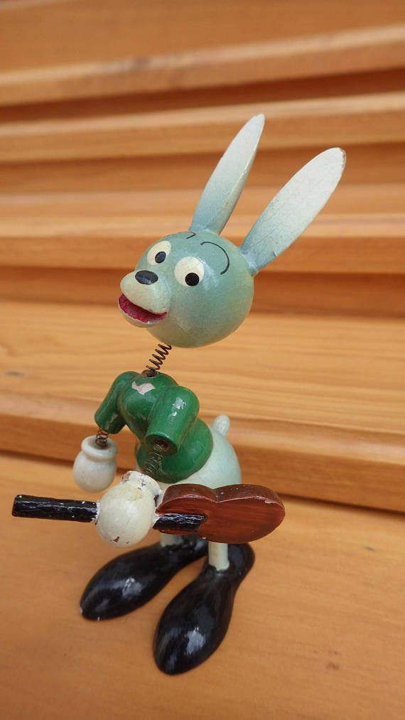 This rascally rabbit is carved from wood and nods his head on a spring while playing the guitar.  Would make a great gift for that special musician in your life.  This vintage toy is marked Vila Made in Spain Patentado.  Believed to be from the 1960s. Similar to the Goula nodder figures of the 1950s-1960s time period made in Spain.  In very nice condition with a little paint loss and discolouring, but the face is perfect. See photos.  All of the items for sale at Bottle Cap Vintage are…