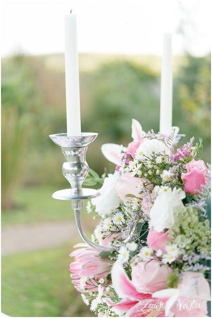 Flower arrangement hanging off arm of silver candelabra