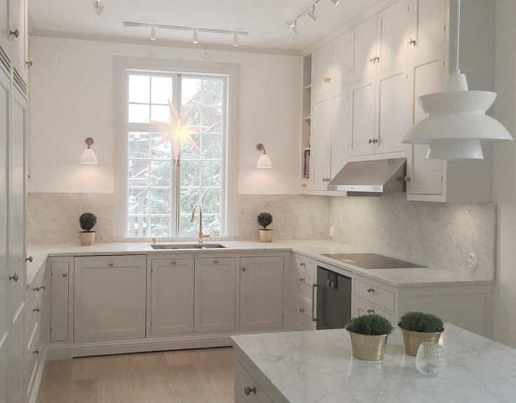 Classic kitchen with a modern vibe. Carrara marble counter tops, Carrara marble back splash. Kitchen island with marble. Light gray cabinets and brass hardware and brass faucet. White washed oak planks floor. Bestlite wall sconces.