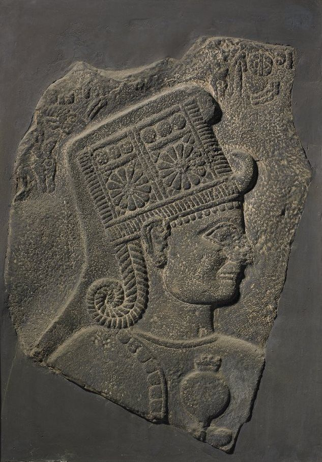 Plaster cast of a Neo-Hittite relief; goddess facing right, wearing elaborate headdress, long hair and holding a flower; hieroglyphic Hittite inscription around top; painted black in imitation of original basalt; mounted in wooden frame. Culture/period:      Neo-Hittite - 10thC BC (original)
