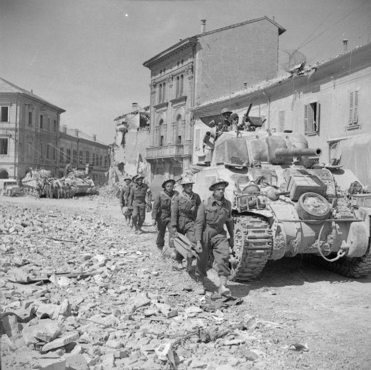 Stretcher bearers pass Sherman tanks in Portomaggiore, 19 April 1945