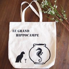 A refined looking cat sips wine and converses with a very big seahorse. Tote bag hand painted by Grafeeq