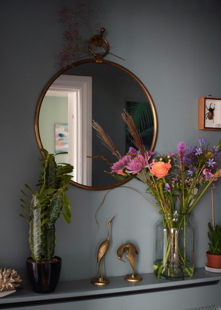 Vintage bohemian eclectic style hallway interior using Farrow & Ball Oval Room Blue with faux cactus and brass mirror