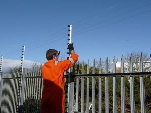Electric fence installer at work on a new installation to help improve perimeter security at a vehicle compound (UK).
