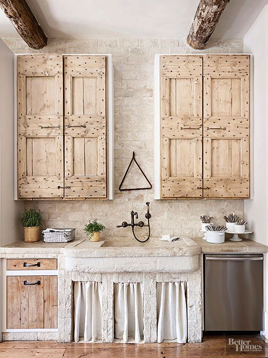 Unfinished lumber is featured in one-of-a-kind cabinetry that boasts a rustic, handmade look. The cabinets work well with an oil-rubbed-bronze faucet, rough stone walls, a carved sink, and, remarkably, a stainless-steel dishwasher.