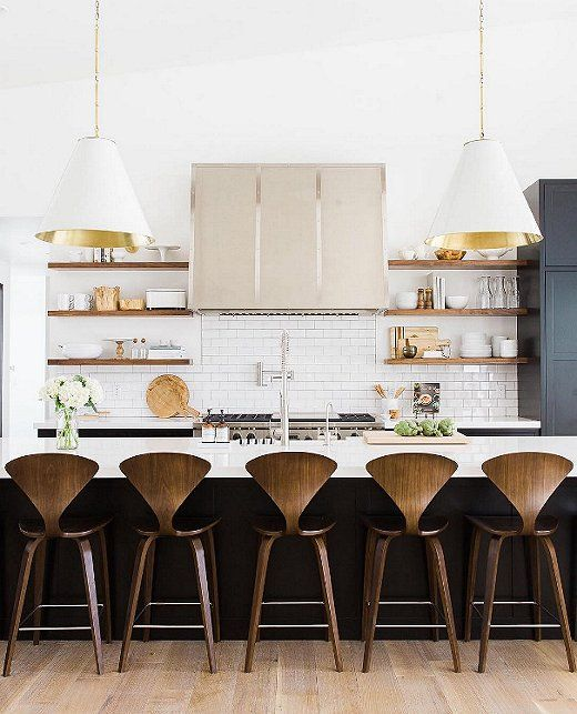 Modern black and white tuxedo kitchen with gold pendant lights and open shelves.
