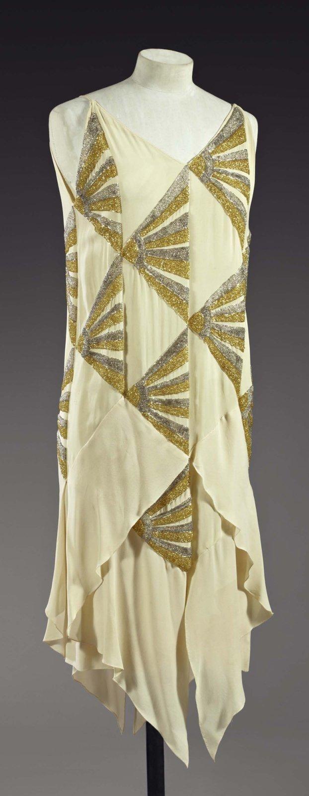 """Madeleine Vionnet Robe du soir """"éventails Japonais"""", 1925 (attribuée à). Robe courte en crêpe romain ivoire rebrodé d'éventails japonais stylisés en dégradés de perles de verre argent et or. Décolleté en """"V"""", volant en pointe devant et derrière. Griffe manquante. Très influencée par les arts décoratifs en particuliers les laques et les kimonos japonais, Madeleine Vionnet s'en inspira dans de nombreuses créations des années 20."""