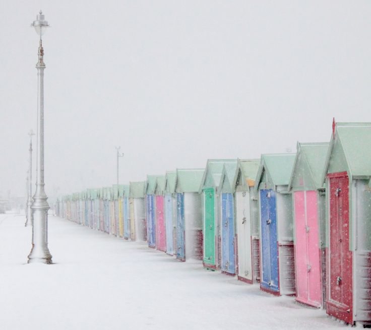 Hove beach huts in the snow: The beach huts are located on Hove promenade and built from wood.