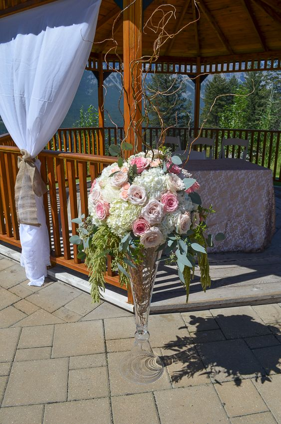 Ceremony arrangement in a tall clarinet vase with white hydrangea, pink roses and hanging green amaranthus for a gazebo wedding ceremony at Silvertip Resort- Canmore, Alberta.  www.flowersbyjanie.com  Flowers by Janie- Calgary & Canmore Wedding Florist