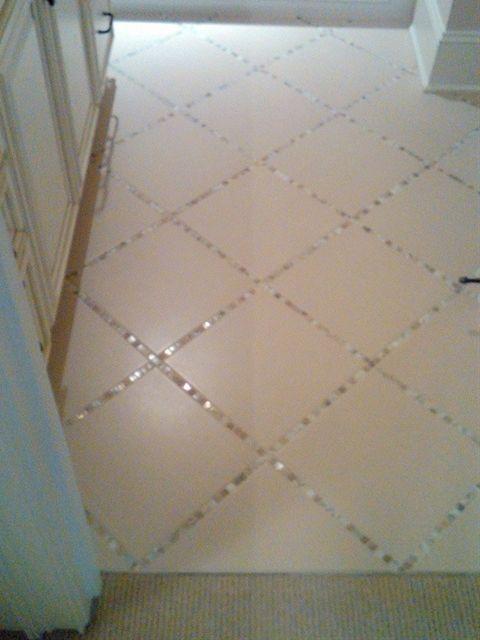 Lay a strip of thin tile used for backsplash in between the floor tiles. Bathroom floor?