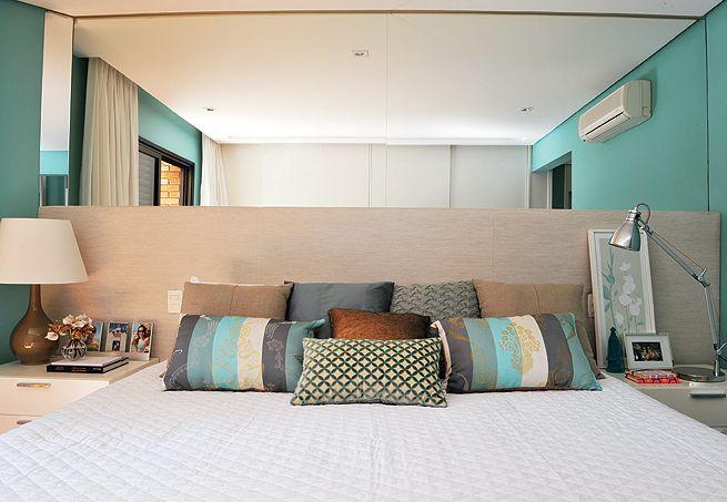 A cabeceira extensa, que ocupa toda a largura do quarto, passa a sensação de um ambiente mais amplo. O espelho acima da cama brinca com a profundidade do cômodo, favorecendo-o  Fotos Marcelo Magnani / Casa  Jardim