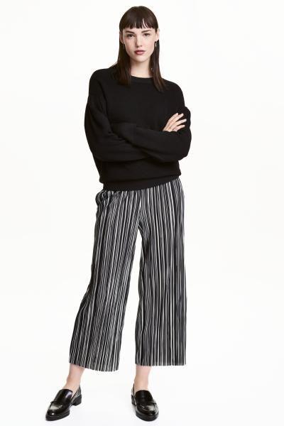 Een wijde, enkellange broek van zacht, geplisseerd tricot met elastiek in de taille, een verlaagd kruis en rechte pijpen met een onafgewerkte rand onderaan.