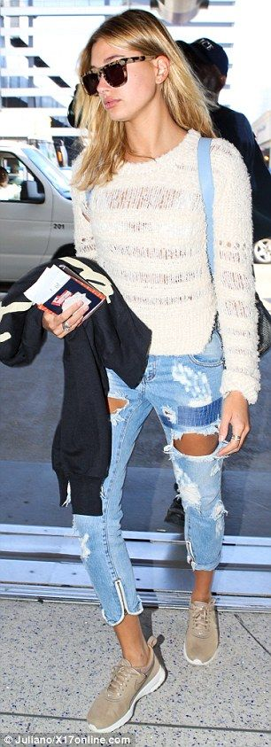 Let it rip: Hailey, 18, flashed her white bra in a knitted jumper, paired with ripped jean...