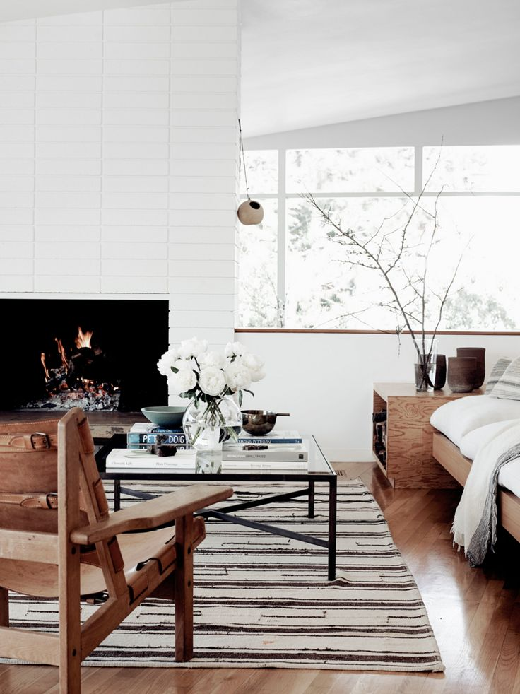 Living room with timber flooring, fireplace and white walls, via Inspiring Spaces via A House in the Hills. Photo Pia Ulin