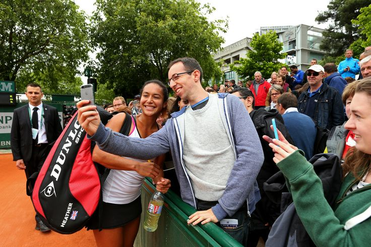 A spectator takes a selfie with Heather Watson of Great Britain as she celebrates victory in her women's singles match against Barbora Zahlavova Strycova of Czech Republic on day three of the French Open at Roland Garros on May 27, 2014 in Paris, France.