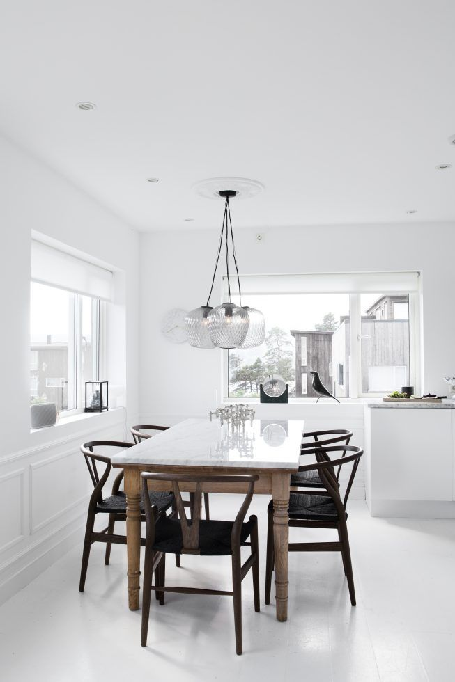 all white kitchen with a marble table and black wishbone chairs by Atelier Ribe…