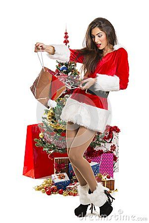 Attractive surprised young lady dressed in sexy Santa outfit opening a present bag near decorated Christmas tree and gifts, isolated on white.